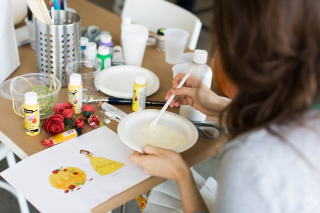 Mixing paint to match a favorite character's costume, using a printed image of Belle from Beauty and the Beast and a sketch of a yellow pumpkin covered in red roses