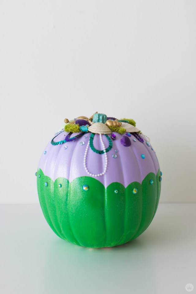Shells, moss, pearls, gems and sequins decorate a lavender and green pumpkin