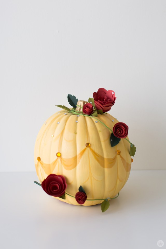 Yellow pumpkin wrapped with artificial red roses and encrusted with yellow gems