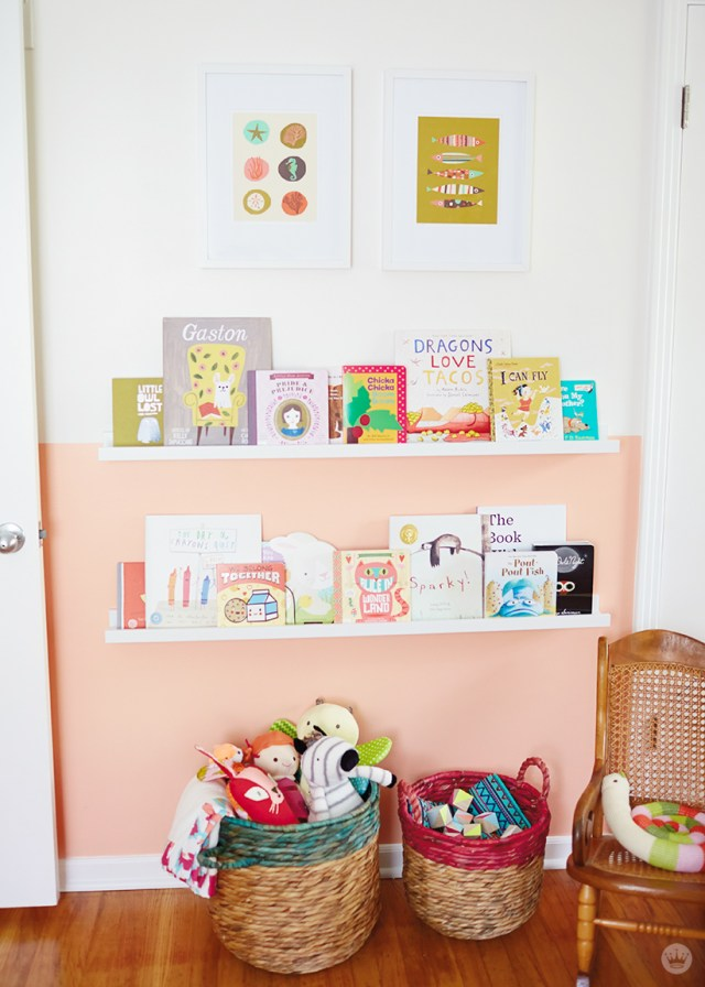 Tips for displaying art: Two framed prints hang over picture ledges filled with a child's books