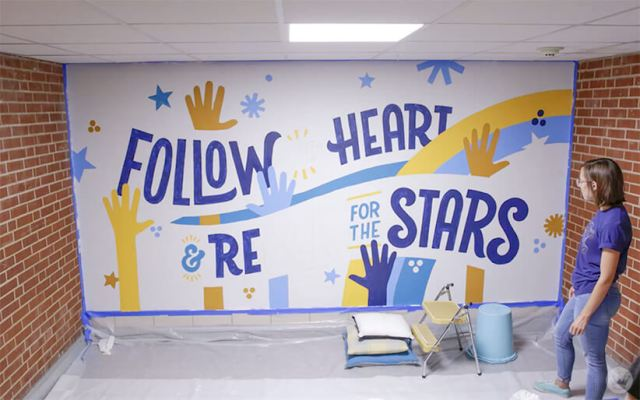 Hallmark artist checking progress on an inspiring mural at a local elementary school
