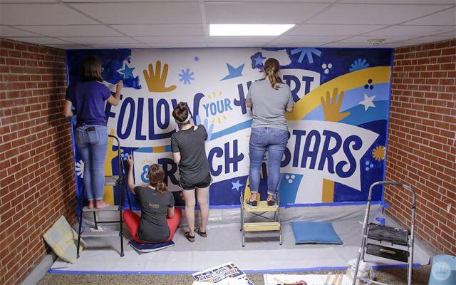 Hallmark artists painting an inspiring mural at a local elementary school