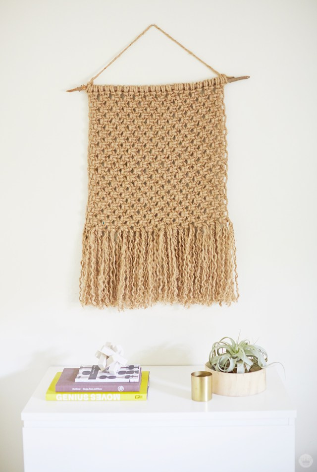Fringed macramé wall hanging displayed on white wall.