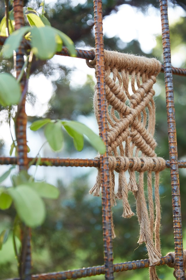 Simple macramé yard art in jute on a rebar trellis.