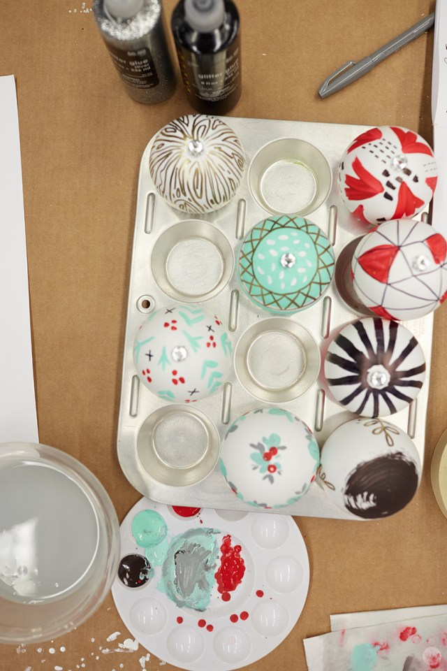 DIY ornament ideas: Hand-painted Christmas ornaments drying in a muffin tin
