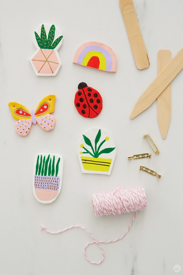finished clay pins with string, pin-backs, and wooden plant labels for the DIY Clay gift attachments | thinkmakeshareblog.com
