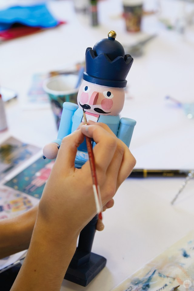 Painting a face on a wooden nutcracker