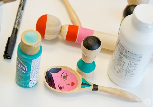 Painted wooden objects with paint bottles.