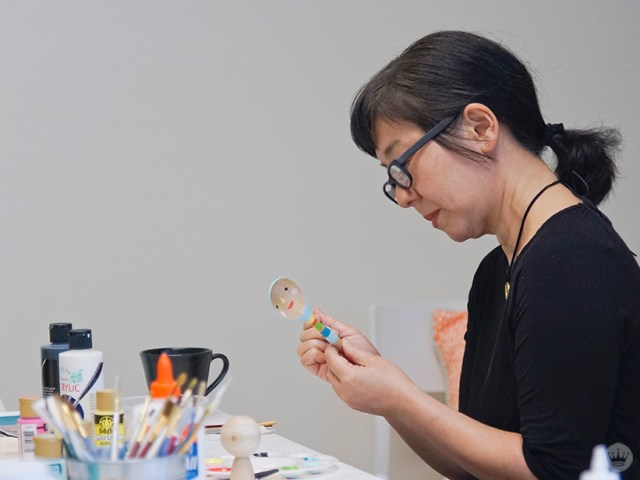 A Hallmark artists works on her painted wooden objects.