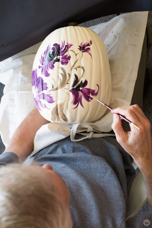 Artist painting large purple flowers on a tall white pumpkin