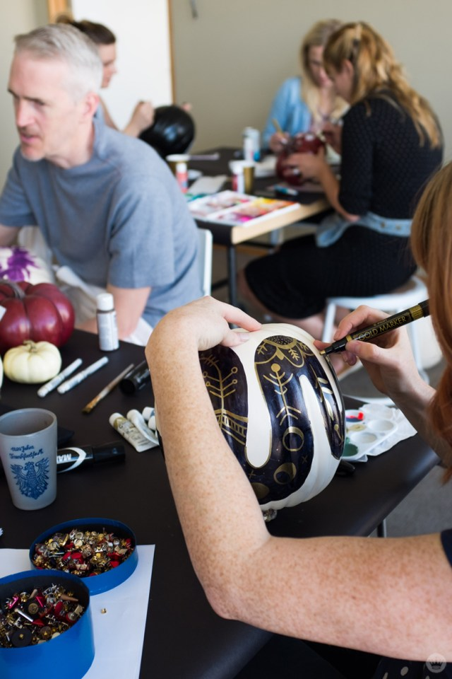 Artist adding gold paint-marker embellishments to a black snake painted on a white pumpkin