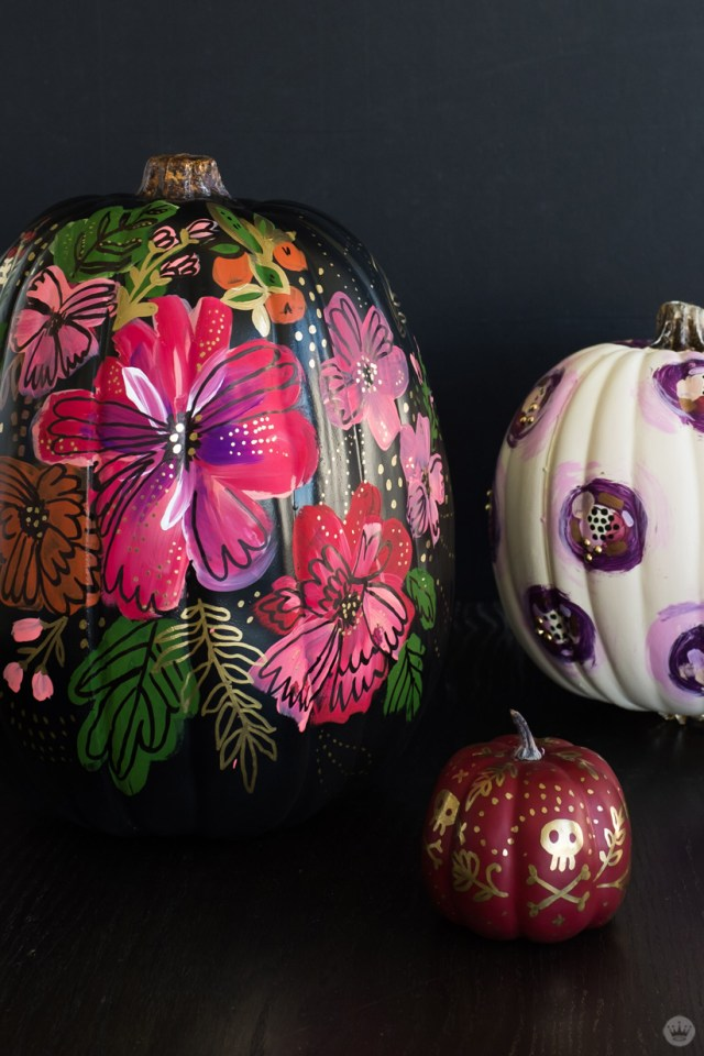 Elegant pumpkin designs: Black pumpkin painted with vivid flowers, white pumpkin decorated with abstract purple pattern, small red pumpkin covered in metallic gold doodles