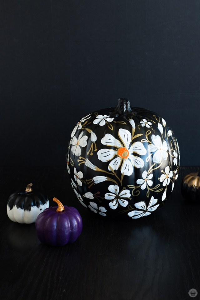 Black painted pumpkin covered in white and gold flowers (also shown: small purple and black/white pumpkin)