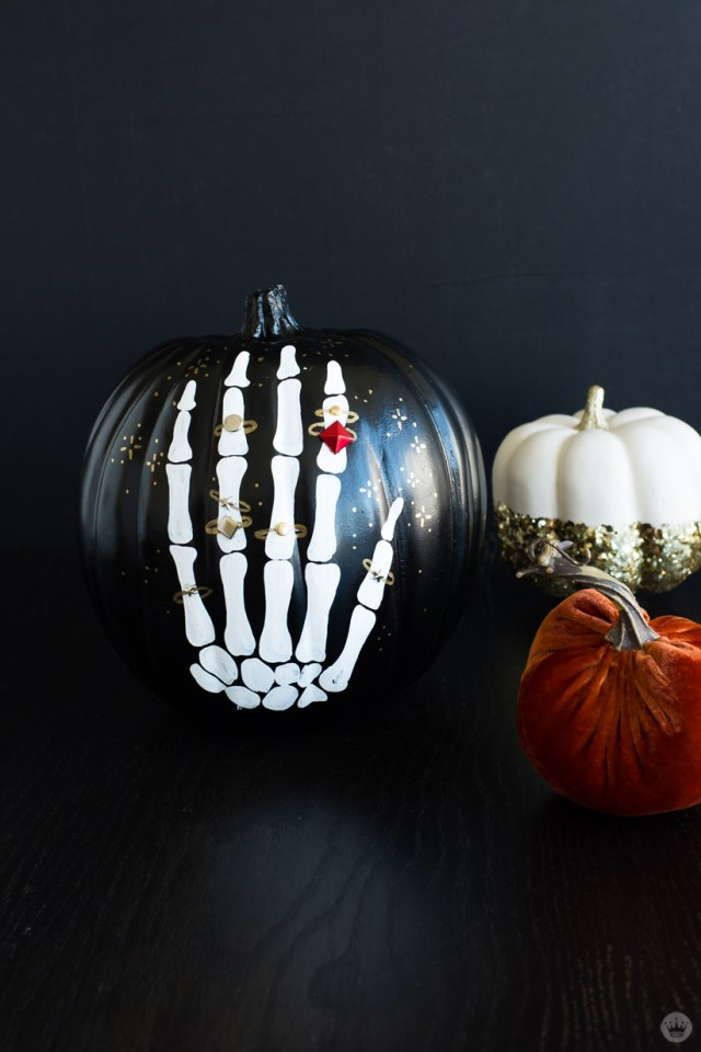 Painted black pumpkin decorated with an embellish skeletal hand—each finger wearing rings, one with a red gemstone (also shown, orange velvet and white/glitter covered pumpkin)