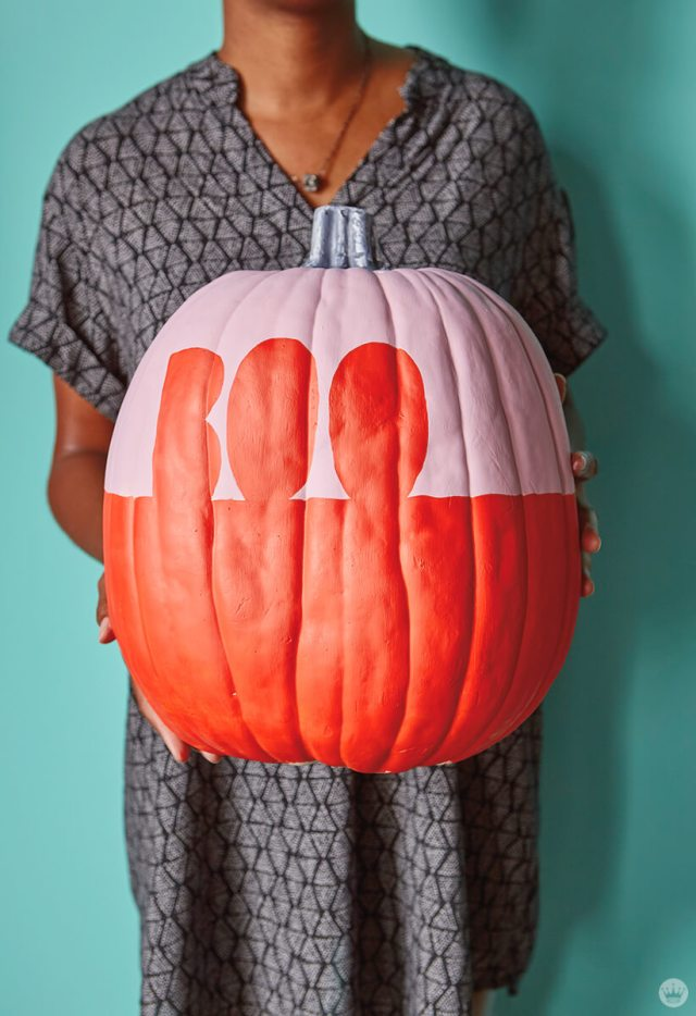 Artist holding pink and orange pumpkin with the word BOO