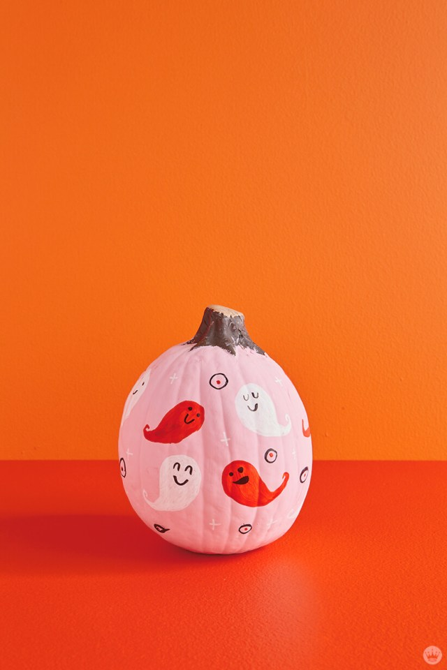 Pink pumpkin painted with white and red ghosts