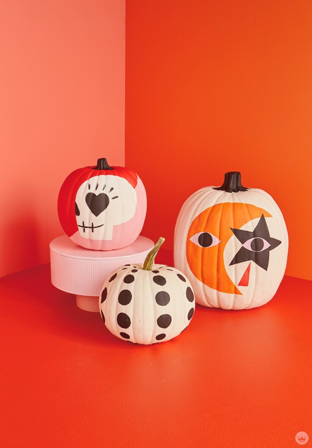 Three pumpkins painted with graphic designs