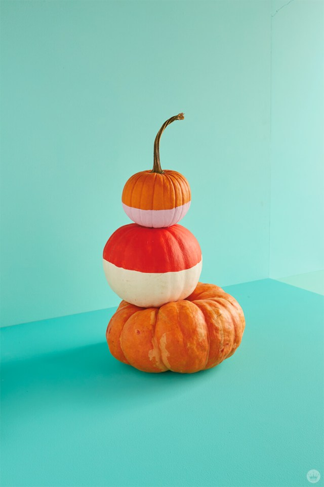 Natural and painted pumpkins stacked three-high