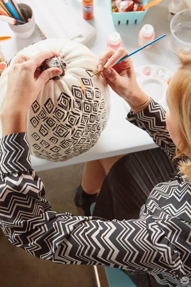 Painting a diamond design on a white pumpkin