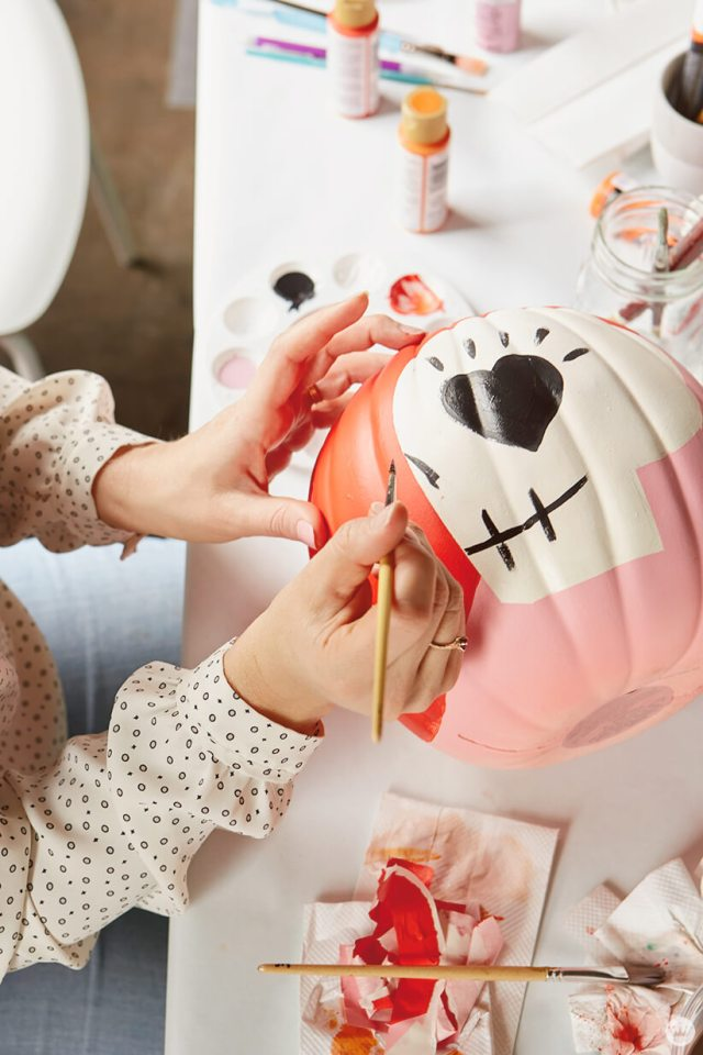 Painting a skull on a pink and orange pumpkin