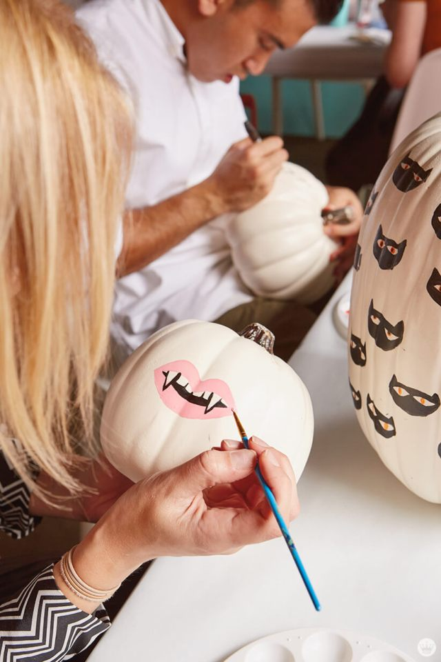 Painting lips and fangs on a small white pumpkin