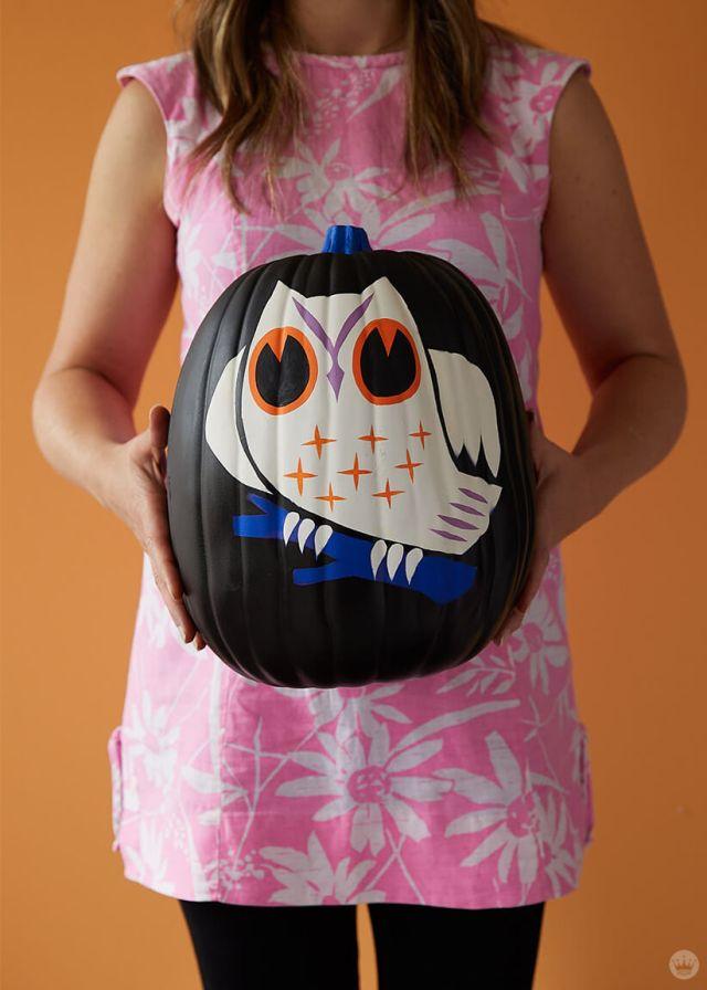 Artist holding black pumpkin with white owl illustration