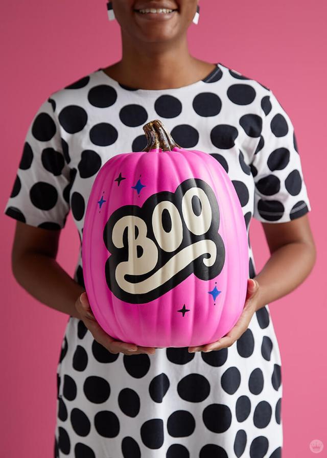 """Artist holding neon pink """"Boo"""" pumpkin"""