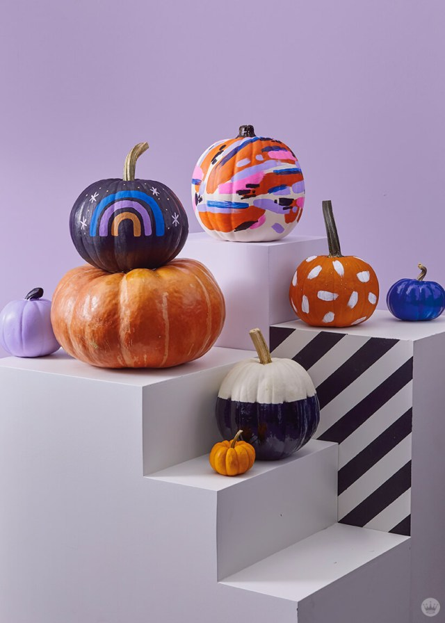 Pumpkins decorated with painted patterns, rainbows, and color blocks