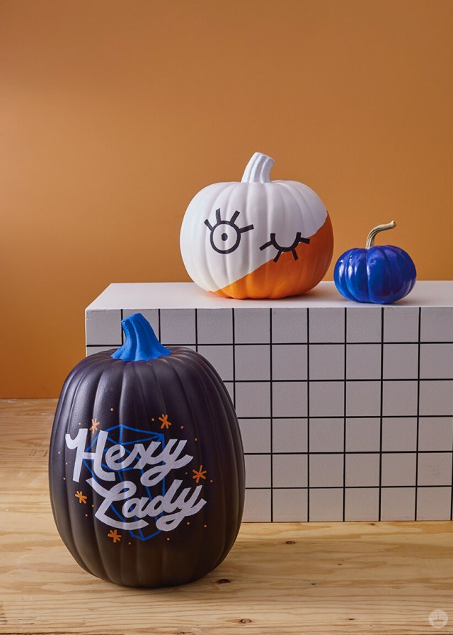 Hexy Lady and Winky Face pumpkins (with a tiny blue pumpkin) against a graphic background