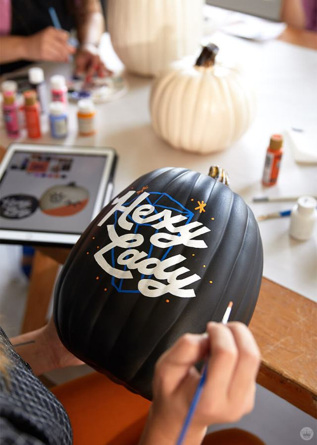 "Painting ""Hexy Lady"" on a black pumpkin"