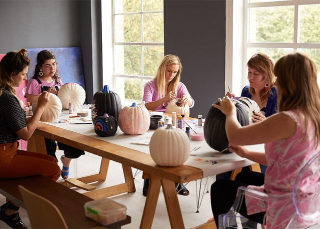 Six Hallmark artists share a table to paint pumpkins