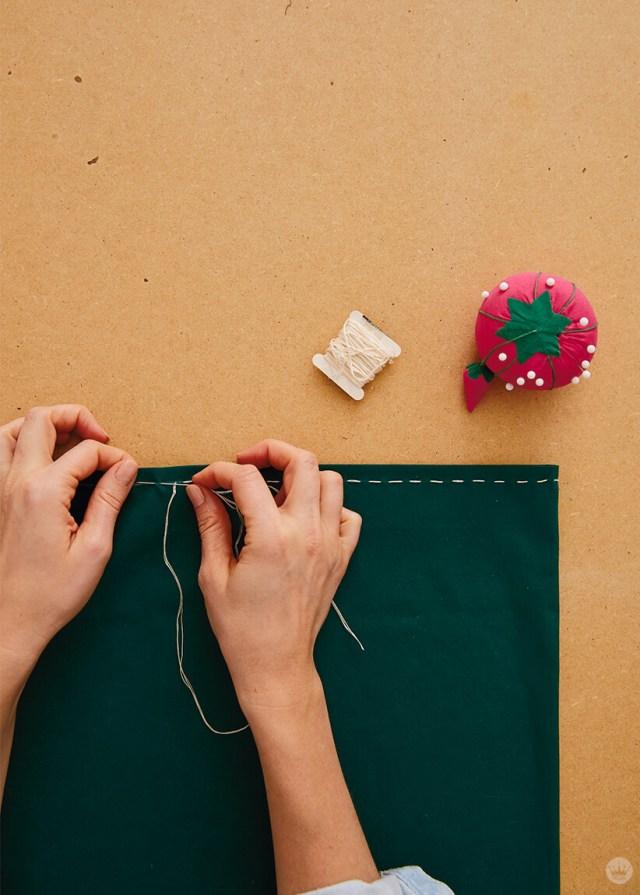 Coudre un point courant sur l'ourlet supérieur d'une taie d'oreiller verte | thinkmakeshareblog.com