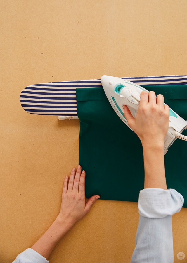 Ironing the hem of a pillowcase to keep it in place | thinkmakeshareblog.com