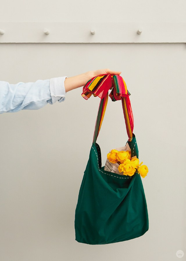 Woman's arm holding green DIY pillowcase tote with fellow roses inside. | thinkmakeshareblog.com