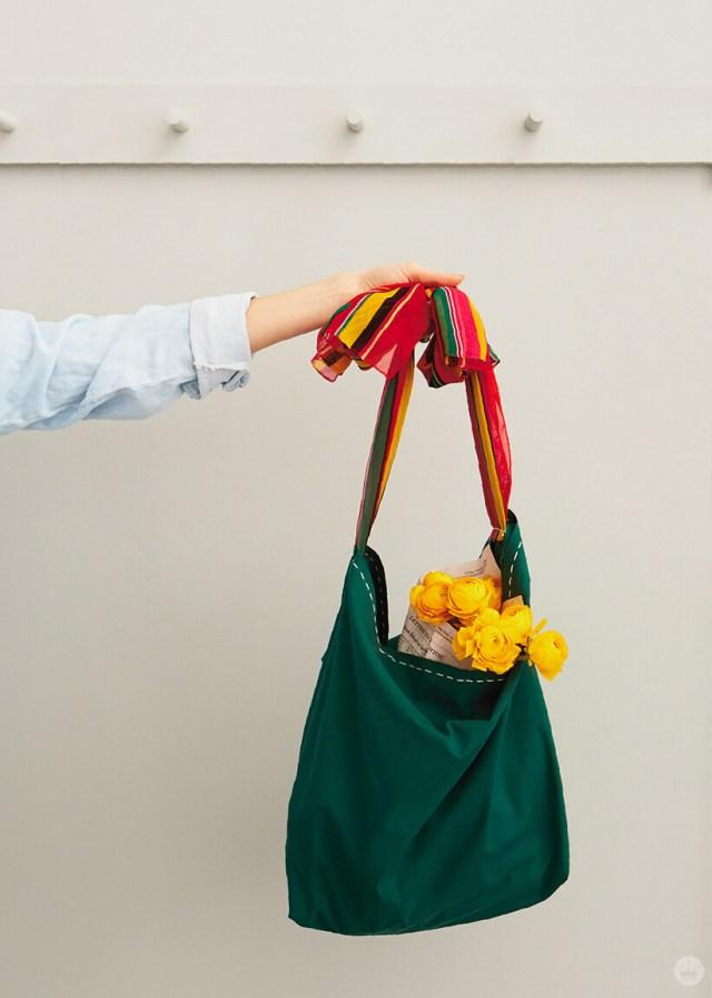 Bras de femme tenant un tote de bricolage vert avec d'autres roses à l'intérieur. | thinkmakeshareblog.com
