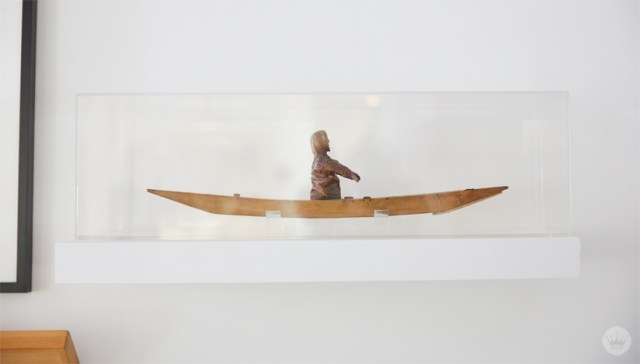 Tips for displaying art: A carving of a figure in a boat is displayed in a plexiglass box