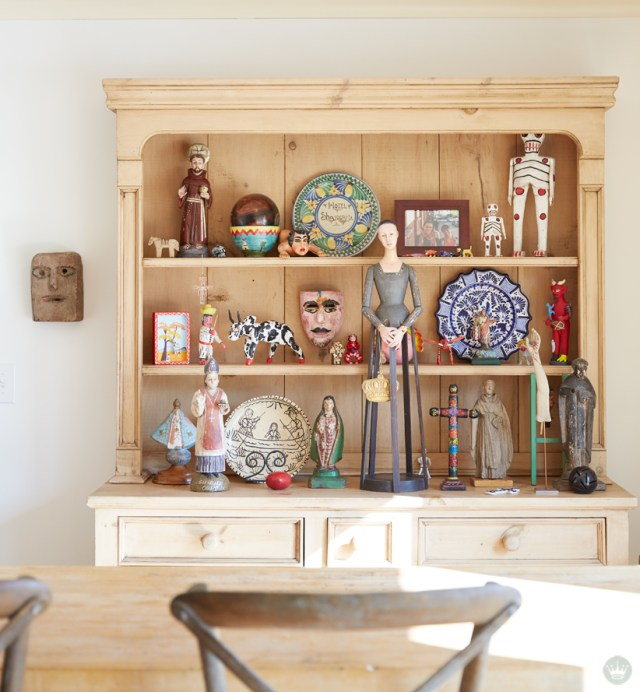Tips for displaying art: A collection of folk art plates and figures is displayed on an open-front cupboard