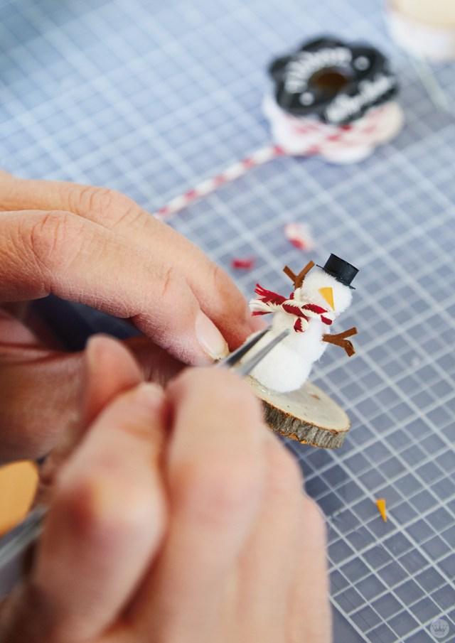 Adding a bakers twine scarf to a tiny snowman made of pom poms