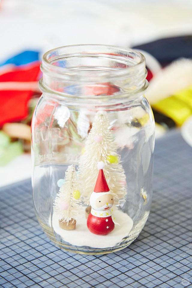 A tiny Santa made of wooden beads inside a mason jar snow globe