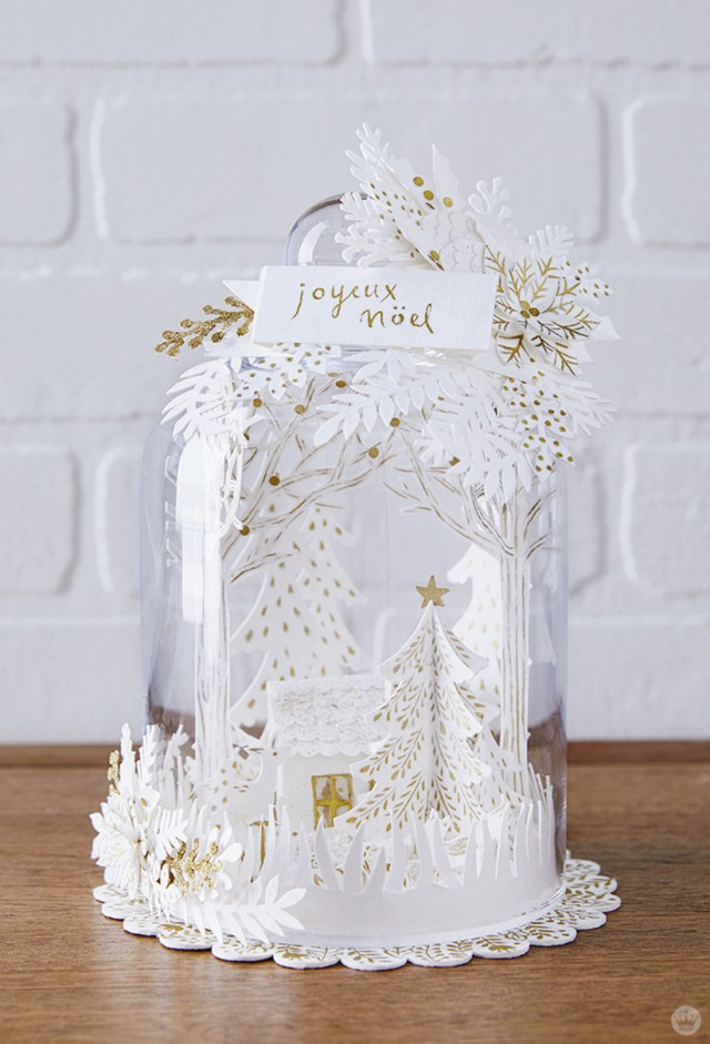 Intricate cut-paper designs inside and outside a glass cloche