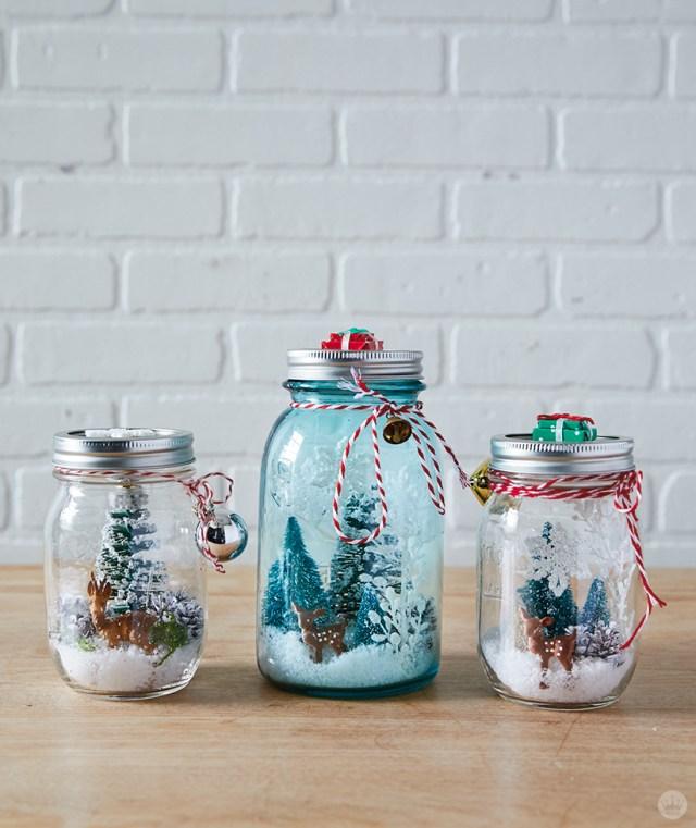 Deer and bottle brush trees inside DIY mason jar snowglobes