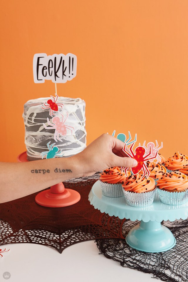 Spiderweb cake and orange-frosted cupcakes with spider toppers
