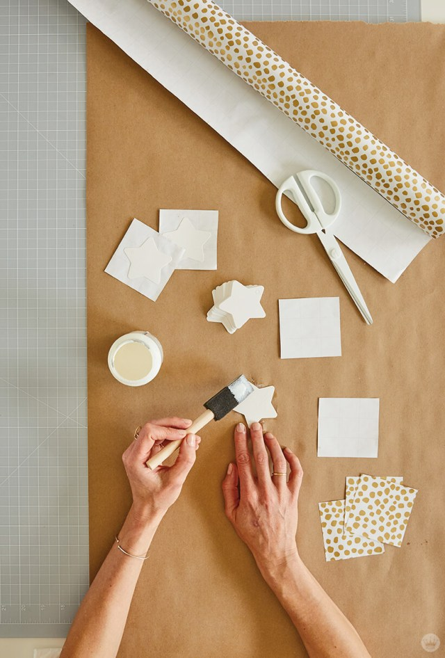 Applying mod podge to cardstock star in order to glue on the gift wrap for the DIY Star Wall Hanging | thinkmakeshareblog.com