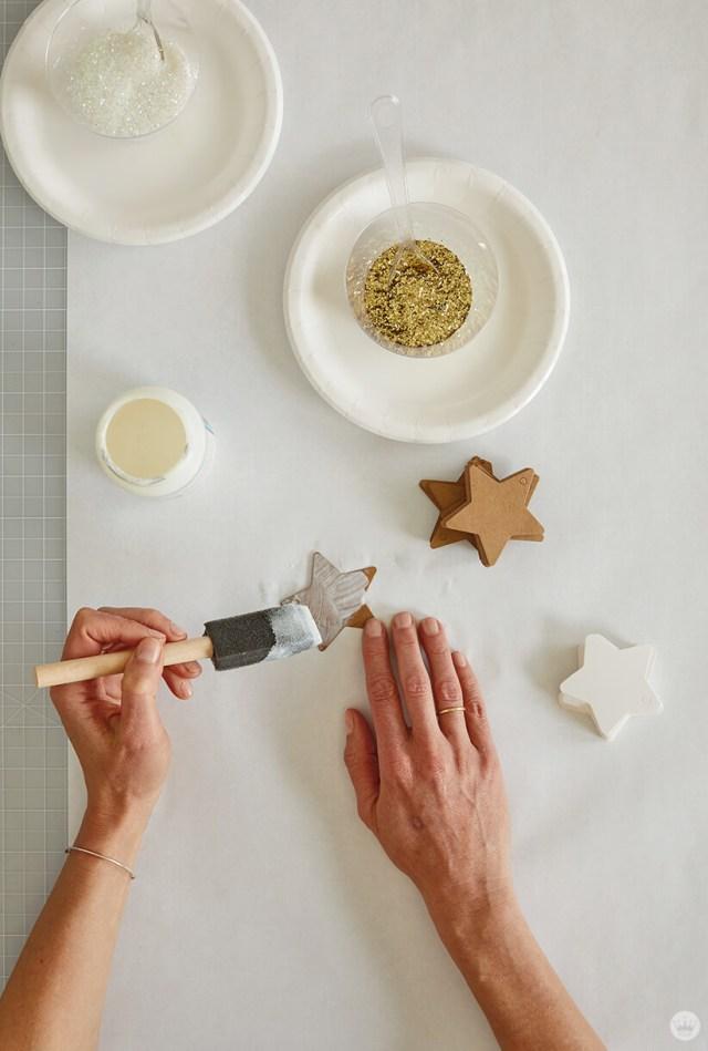 Application de mod podge sur un côté des étoiles découpées pour la décoration murale DIY Star | thinkmakeshareblog.com