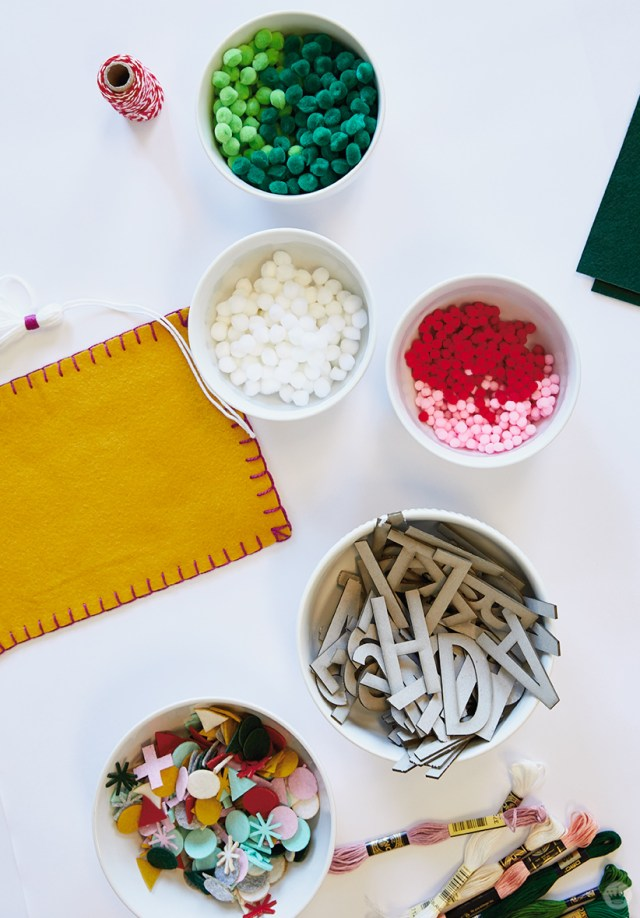 Supplies for DIY Christmas stockings: pom poms, appliqués, letters