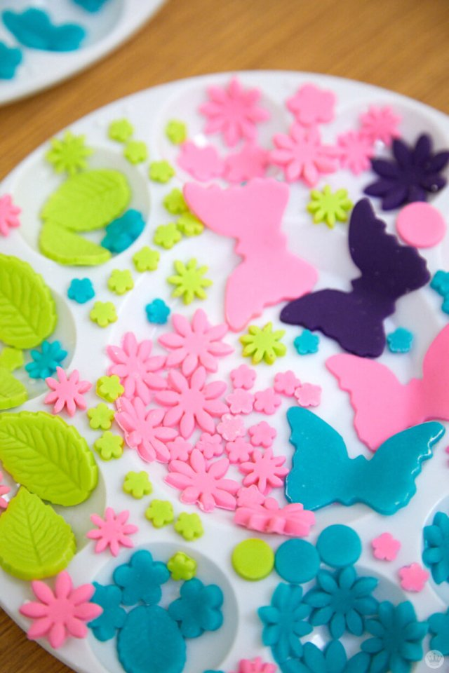 Color fondant cut into flowers, leaves, and butterflies