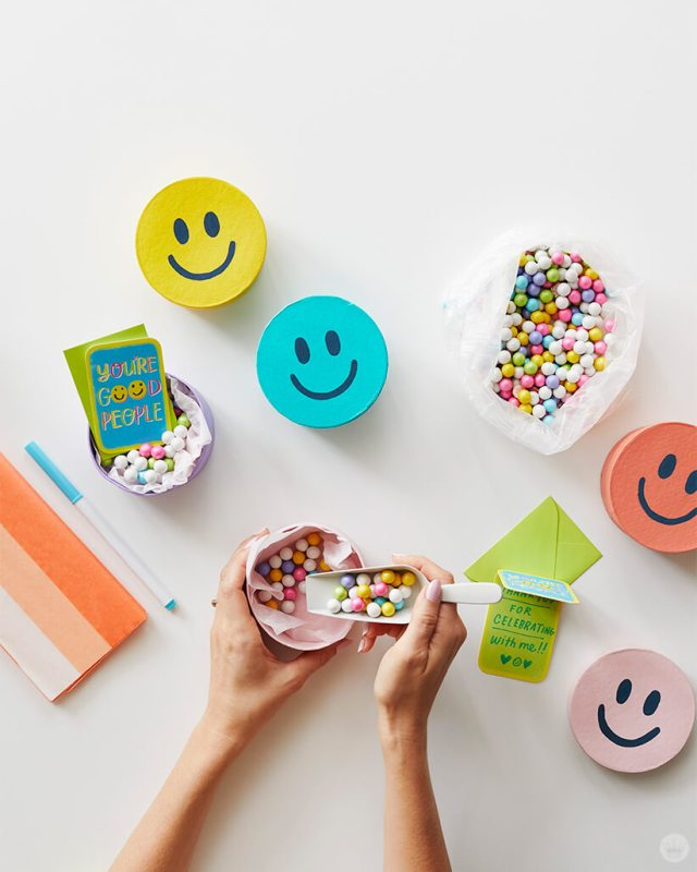 Yellow, blue, coral, pink and lavender Smiley Face Treat Boxes being filled with pastel candies.
