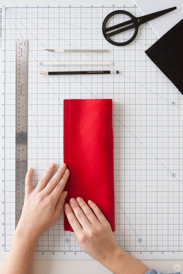 Folding red felt in half for a DIY Felt Pennant Banner