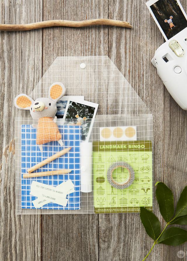 DIY Travel Game kit with instant camera and photos, stuffed mouse from Hallmark Baby, notebooks, printed captions, glue stick, washi tape, dot stickers, and Landmark Bingo cards,