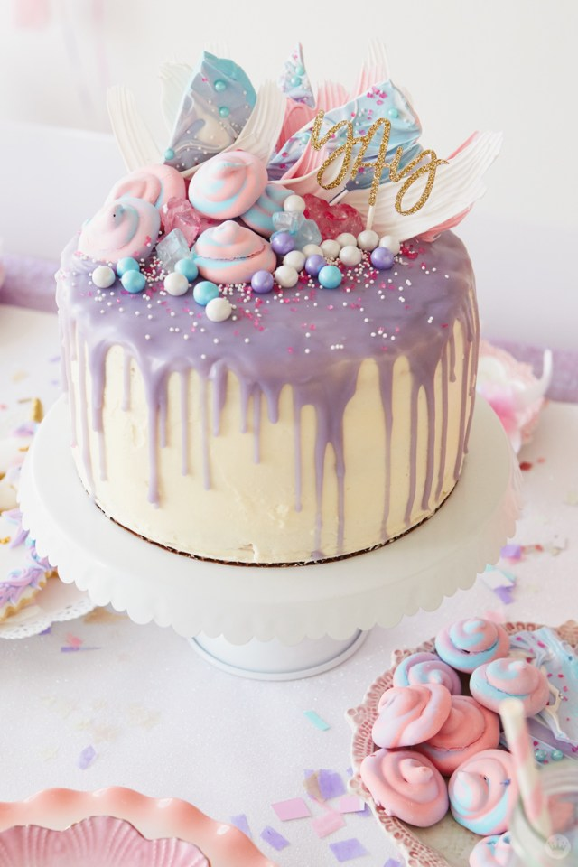 "Cake frosted in white with lavender drizzle; topped with pink and blue sprinkles, meringues, and unicorn bark and ""yay"" lettering in gold glitter"